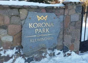 szyld Korona Park namurze przy bramie wjazdowej